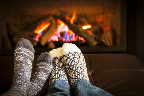 Couple relaxing their feet in front of a fire during the winter
