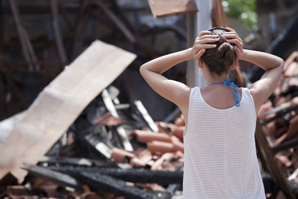 Woman upset wtih her hands to her head over a destroyed house from a disaster